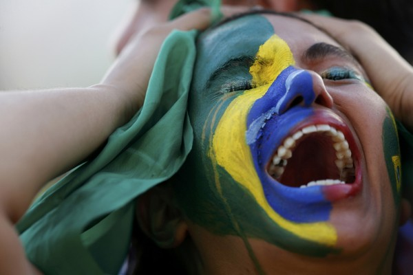 A fan of Brazil reacts while watching a broadcast of the 2014 World Cup semi-final against Germany at the Fan Fest in Brasilia