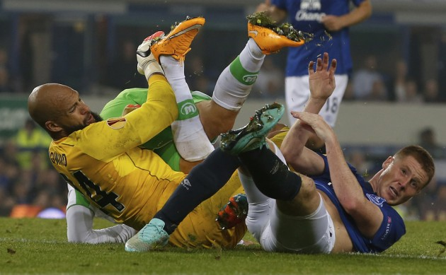 Everton's Howard saves the ball from VfL Wolfsburg's Hunt with the help of teammate McCarthy during their Europa League soccer match at Goodison Park in Liverpool